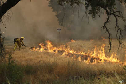 firefighter with Cal Fire Mendocino Unit takes a rake to flames as a wildfire advances, July 30, 2018, in Lakeport, California.