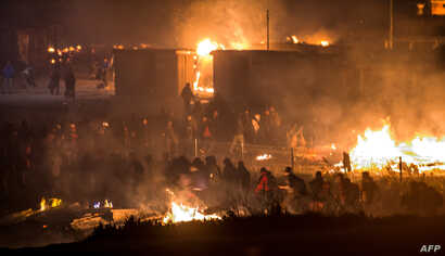 "Migrants evacuate as a huge fire blazes through the Grande-Synthe migrant camp outside the northern French city of Dunkirk late April 10, 2017, reducing it to ""a heap of ashes,"" the regional chief said."