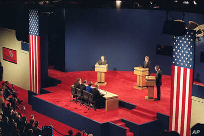 Presidential candidates, from left, Ross Perot, Bill Clinton, and President George Bush, participate in the first presidential debate in St. Louis, Mo., Oct. 12, 1992.