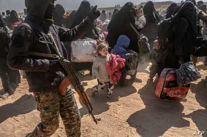 Women and children evacuated from the Islamic State group's embattled holdout of Baghuz arrive at a screening area held by the U.S.-backed Kurdish-led Syrian Democratic Forces, in the eastern Syrian province of Deir el-Zour, March 6, 2019.