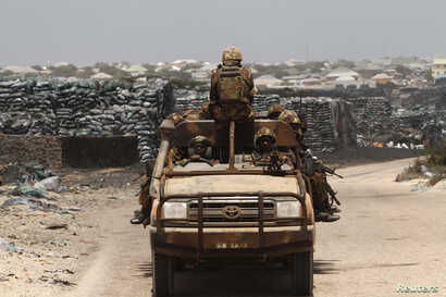 Kenya Defence Force (KDF) soldiers, serving in the African Union Mission in Somalia (AMISOM), patrol past stockpiles of charcoal near the Kismayo sea port town in lower Juba region, Somalia, Feb. 27, 2013.
