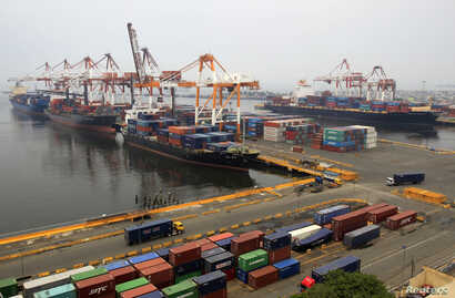 FILE - Cargo vessels wait to unload containers, while docked at the port in Manila, Aug. 20, 2014.