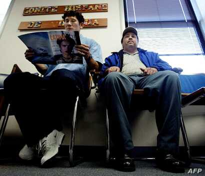 FILE - A Salvadoran national, left, accompanied by a friend (R), waits in the lobby of the Comite Hispano de Virgina, in Falls Church, Virginia, Nov. 11, 2002, to get help with his US immigration paperwork to extend his Temporary Protected Status (TP...