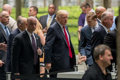 Republican presidential candidate Donald Trump, center, arrives to attend a ceremony at the National September 11 Memorial, in New York, Sept. 11, 2016, on the 15th anniversary of the Sept. 11 attacks.