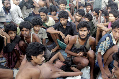 migrants including Myanmar's Rohingya Muslims sit on the deck of their boat as they wait to be rescued by Acehnese fishermen on the sea off East Aceh, Indonesia. Myanmar called sad and regrettable a move by the United States to place the country on ...