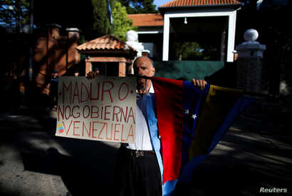 """A Venezuelan demonstrator holds a banner that reads """"[President Nicolas] Maduro doesn't govern Venezuela"""" outside the Olivos Presidential Residence, in Buenos Aires, Argentina, March 1, 2019."""