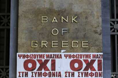 """Posters reading """"We vote en masse, no the agreement'' are seen under Bank of Greece logo in Athens, July 3, 2015."""