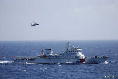 Chinese ship and helicopter are seen during a search and rescue exercise near Qilian Yu subgroup in the Paracel Islands, which is known in China as Xisha Islands, South China Sea, July 14, 2016.