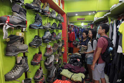 FILE - Tourists from Singapore visit the Everest Base Camp shop for trekking gear in Kathmandu, Nepal, April 20, 2016. After two hard years for mountaineering, more than 200 climbers have scaled the daunting mountain in the past 10 days, sending a wa...