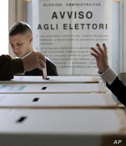 FILE - A voter casts his ballot in a polling station, in Rome.