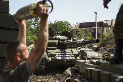 FILE - A pro-Russia rebel loads shells onto a tank near Donetsk, eastern Ukraine, June 12, 2015.