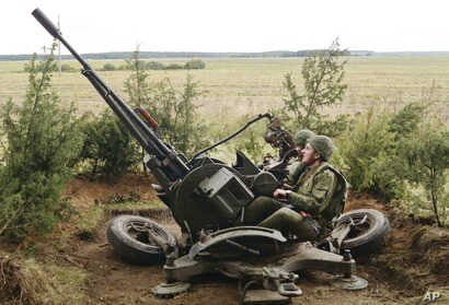 In this photo taken Sept. 14, 2017, Belarus' soldiers aim an anti-aircraft gun at a training ground at an undisclosed location in Belarus. Russia and Belarus began major war games this week thousands of troops, tanks and aircraft.