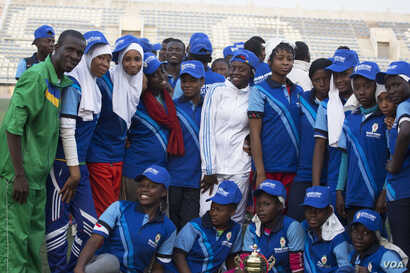 The Basic College high school all-girl rugby team smiles at the end of the tournament. They played a scoreless game, but they still received a trophy. (Photo by Chika Oduah/VOA)