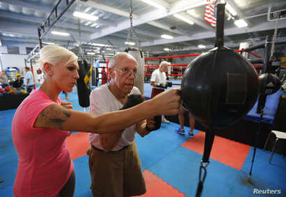 Parkinson's patient Jim Coppula gets some pointers from his daughter Ellen as he works out on a bag during his Rock Steady Boxing class in Costa Mesa, California September 18, 2013. According to the Parkinson's Disease Foundation, research has shown ...