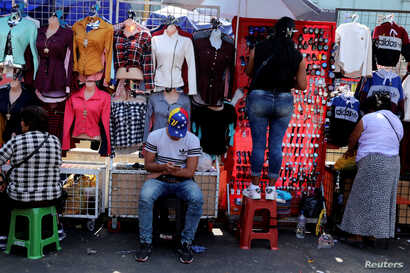 A migrant from Venezuela, sells clothing at Gamarra textile cluster in Lima's district of La Victoria in Lima, Peru, May 10, 2018.