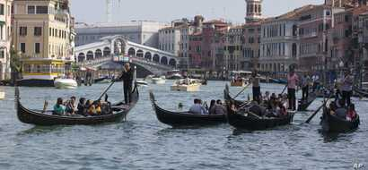 FILE - Tourists tour the Grand Canal on traditional Gondola Venetian boats, in Venice, Italy, Sept. 28, 2014.