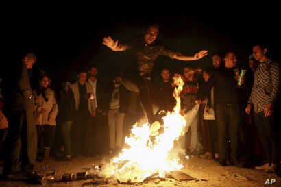 """An Iranian man jumps over a bonfire during a celebration, known as """"Chaharshanbe Souri,"""" or Wednesday Feast, marking the eve of the last Wednesday of the solar Persian year, March 19, 2019 in Tehran."""