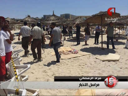 In this screen grab taken from video provided by Tunisia TV1, injured people are treated on a Tunisian beach at the resort town of Sousse, June 26, 2015.