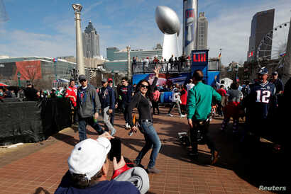 A woman poses near a giant replica of the Vince Lombardi Trophy during an NFL fan celebration in Centennial Park outside Mercedes Benz Stadium ahead of Super Bowl LIII in Atlanta, Georgia, February 2, 2019.
