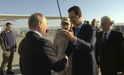 FILE - In a frame grab made available by Russian Presidential TV, Syrian President Bashar Assad, right, greets Russian President Vladimir Putin upon his arrival to the Hemeimeem air base in Syria, Dec. 11, 2017.