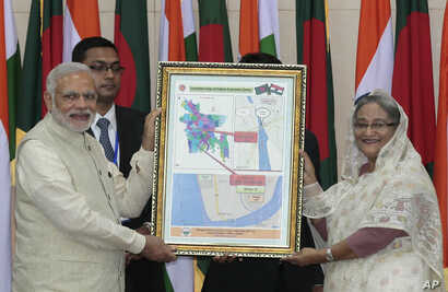 Bangladesh's Prime Minister Sheikh Hasina, right, and Indian Prime Minister Narendra Modi hold a location map of Indian Economic Zones during an agreement program in Dhaka, Bangladesh, June 6, 2015.