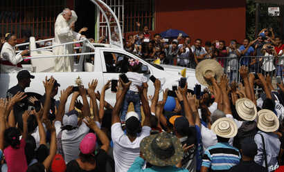 Residents line the roadside to greet Pope Francis as he rides past in his popemobile en route to Las Garzas de Pacora detention center for minors, in Panama, Jan. 25, 2019.