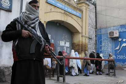 Security guards stand alert around schools and colleges following an attack on Bacha Khan University, in Peshawar, Pakistan,  Jan. 21, 2016.