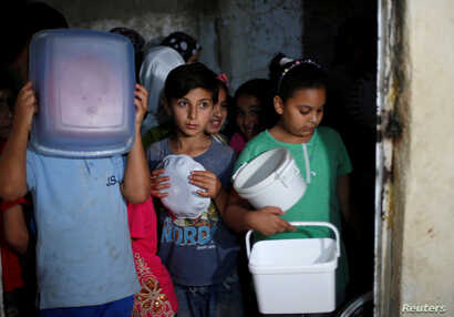 Children wait for meals provided through the initiative, Family Kitchen, which packages excess foods from five-star hotels to underprivileged families during the holy month of Ramadan, in Al-Baqaa Palestinian refugee camp, near Amman, Jordan, June 10...
