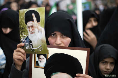 FILE - A woman holds pictures of Iran's Supreme Leader Ayatollah Ali Khamenei (top) and late Leader Ayatollah Ruhollah Khomeini during a rally to mark the 32nd anniversary of the Islamic Revolution in Qom, February 11, 2011. REUTERS/Morteza Nikoubazl...
