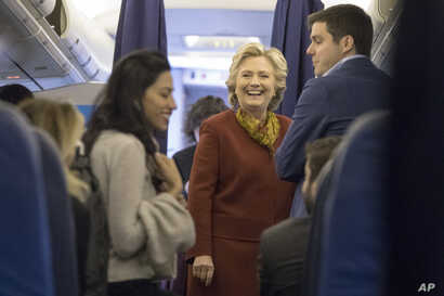 Democratic presidential nominee Hillary Clinton, center, speaks to aides, including Huma Abedin, left, aboard her campaign plane at Westchester County Airport in White Plains, N.Y., Oct. 22, 2016.