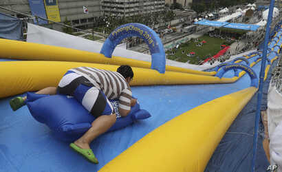 A man slides down a 22-meter-high and 300-meter-long water slide during the event called Bobsleigh in Seoul, South Korea, Aug. 19, 2017. The water slide is set up to promote the 2018 Pyeongchang Winter Olympic Games.