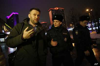 Russian opposition activist Alexei Navalny, left, is briefly detained by police officers after defying his house arrest to speak on Radio Ekho Moskvy in Moscow Jan. 14, 2015.
