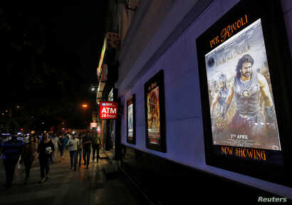 """People walk past a poster of an Indian movie """"Baahubali: The Beginning.""""  """"Baahubali 2"""" is in the works with more magical kingdoms and rampaging armies. ."""