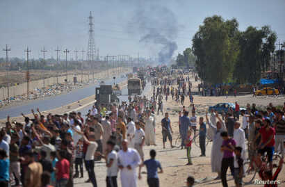 Iraqi people gather on the road as they welcome Iraqi security forces members, who continue to advance in military vehicles in Kirkuk, Iraq, Oct. 16, 2017.