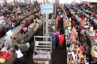 """People shop at a market in Luanda, Angola, Jan. 19, 2018. Angolan President Joao Lourenco was elected five months ago promising an """"economic miracle"""". But the path to transforming the oil-dependent country's system will be long and difficult."""