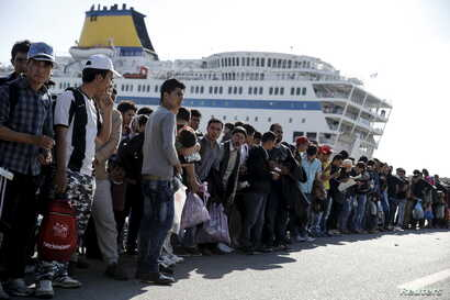 Refugees and migrants line up to board buses at the Greek port of Piraeus, near Athens, Oct. 15, 2015. They were among nearly 2,500 refugees and migrants arriving from Lesbos on the passenger ferry, Eleftherios Venizelos.
