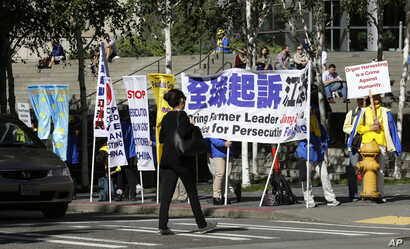Pedestrians pass by as demonstrators with the Falun Gong protest group stand near the hotel where Chinese President Xi Jinping is staying Tuesday, Sept. 22, 2015.