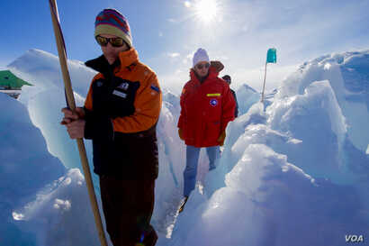 A guide leads U.S. Secretary of State John Kerry through the zone where ice crashes into land outside Scott Base, the New Zealand research station in the Antarctic, Nov. 12, 2016,