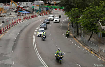 Police take part in a motorcade rehearsal in front of the Hong Kong Convention and Exhibition Center, where Chinese President Xi Jinping will attend a swearing-in ceremony during the 20th anniversary of the territory's handover to Chinese rule in Hon...