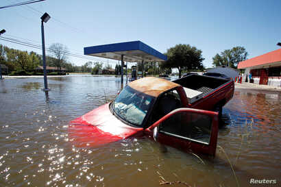 An abandoned truck lies in submerged waters after Hurricane Matthew hit Lumberton, North Carolina, Oct. 9, 2016.