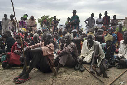 FILE - South Sudanese, displaced by conflict that has raged since late 2013, are seen outside of a U.N. protected camp, in Bentiu, South Sudan, June 18, 2017.