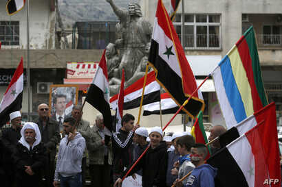 FILE - Residents of the Golan Heights wave Syrian and Druze flags as they gather in front of a portrait of the Syrian President Bashar al-Assad during a protest against the backing of Israel's capture of the Golan Heights by the U.S. president, in th...
