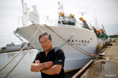 Shigeru Saito, captain of the squid fishing ship Hosei-Maru No.58, poses for a photograph in front of his ship at a port in Sakata, Japan, June 5, 2018.