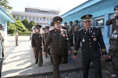 In this photo provided by the South Korea Defense Ministry, North Korean Lt. Gen. An Ik San, center, crosses to southern side for the meeting with South Korea at the border village of Panmunjom, South Korea, July 31, 2018.