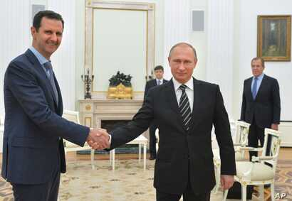 FILE - Russian President Vladimir Putin, center, shakes hand with Syrian President Bashar Assad as Russian Foreign Minister Sergey Lavrov, right, looks on in the Kremlin in Moscow,Oct. 20, 2015.