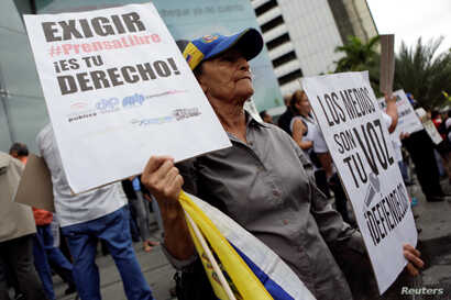 "A woman holds placards during a rally to commemorate World Press Freedom Day in Caracas, Venezuela, May 3, 2016. The placards read, ""Demanding free press is your right"" (L) and ""The media are your voice. Defend them."""