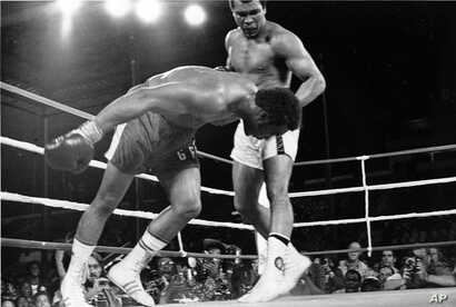 FILE - An Oct. 30, 1974 file photo shows Challenger Muhammad Ali watching as defending world champion George Foreman goes down to the canvas in the eighth round of their WBA/WBC championship match in Kinshasa, Zaire.