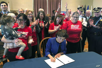 FILE -  Cheers erupt as Rhode Island Gov. Gina Raimondo signs an executive order Feb. 26, 2018, in Warwick, R.I., to establish a new policy to try to keep guns away from people who show warning signs of violence.
