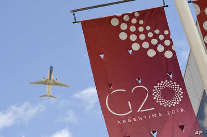 A jet liner flies over the G-20 summit venue at the Costa Salguero Center in Buenos Aires, Argentina, Nov. 28, 2018.