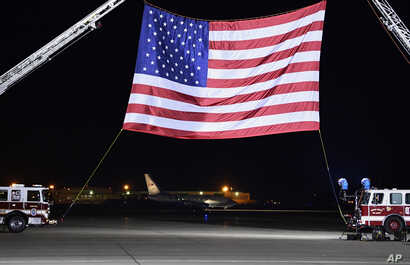 A U.S. government plane, seen in the background below the flag, carrying three Americans freed from captivity in North Korea arrives at Andrews Air Force Base, Md., May 10, 2018.